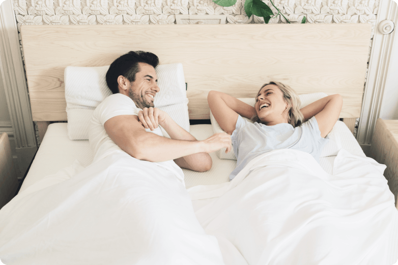 Male and Female smiling happily on a Ecosa mattress